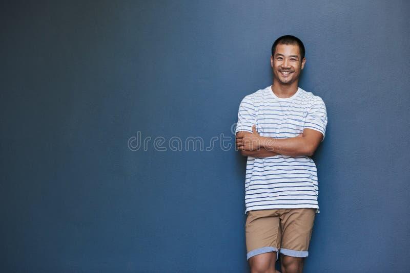 Glimlachende jonge Aziatische mens met een gelegde achterhouding royalty-vrije stock fotografie