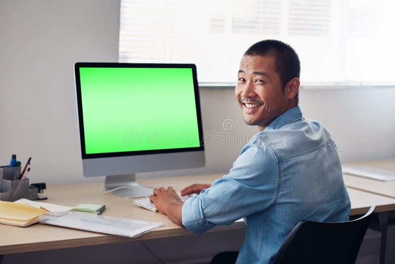 Glimlachende jonge Aziatische ontwerper aan het werk aangaande een bureaucomputer stock afbeelding