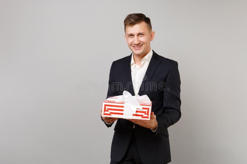 Glimlachende jonge bedrijfsmens die in kostuum rode gestreepte huidige die doos met giftlint houden op grijze achtergrond wordt g royalty-vrije stock afbeeldingen
