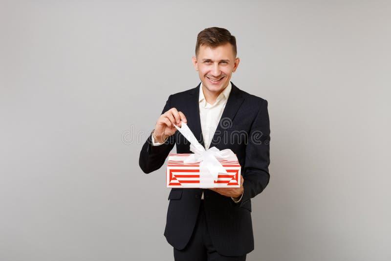 Glimlachende jonge bedrijfsmens die in kostuum rode gestreepte huidige doos met giftlint opent die op grijze achtergrond wordt ge royalty-vrije stock afbeeldingen