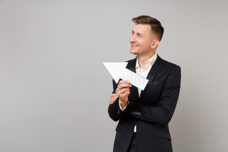 Glimlachende jonge bedrijfsmens in klassiek zwart kostuum, overhemd die die en opzij met pijl kijken tonen op grijze muur wordt g stock afbeelding