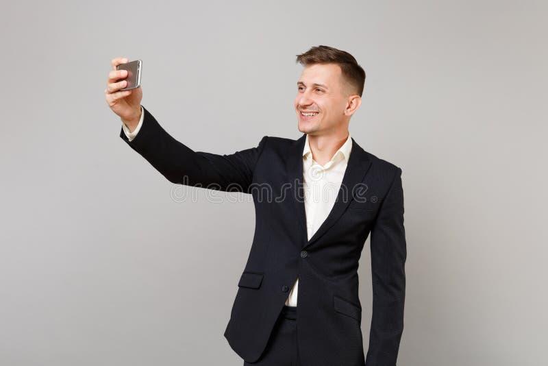 Glimlachende jonge bedrijfsmens in klassiek zwart kostuum, overhemd die nemend selfie schot op mobiele telefoon doen die op grijs royalty-vrije stock afbeeldingen