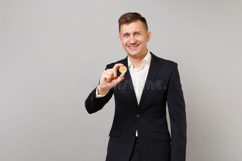 Glimlachende jonge bedrijfsmens in klassieke zwarte kostuum en overhemdsholding bitcoin, toekomstige die munt op grijze muur word stock afbeelding