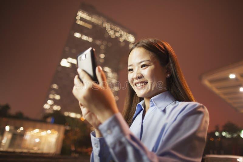 Glimlachende jonge bedrijfsvrouw die haar mobiele telefoon buiten bij nacht bekijken stock fotografie