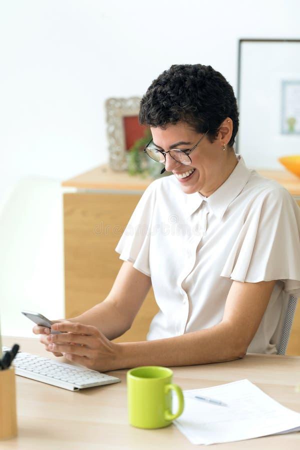 Glimlachende jonge bedrijfsvrouw die haar smartphone gebruiken terwijl het werken met laptop in het bureau royalty-vrije stock fotografie