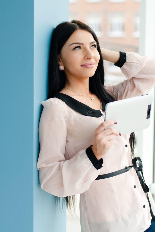 Glimlachende jonge bedrijfsvrouw die tabletpc met behulp van terwijl status ontspannen dichtbij venster op haar kantoor royalty-vrije stock foto's