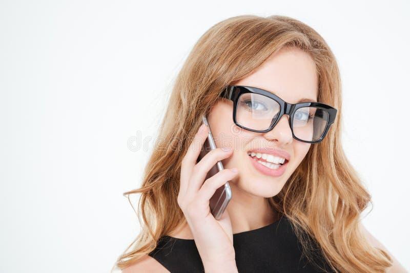 Glimlachende jonge bedrijfsvrouw in glazen die op celtelefoon spreken royalty-vrije stock afbeeldingen