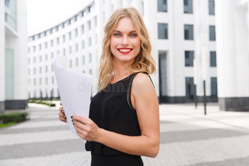 Glimlachende jonge bedrijfsvrouw met blond haar en rode lippenstift royalty-vrije stock fotografie