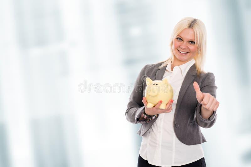 Glimlachende jonge bedrijfsvrouw met omhoog spaarvarken en duim royalty-vrije stock afbeelding