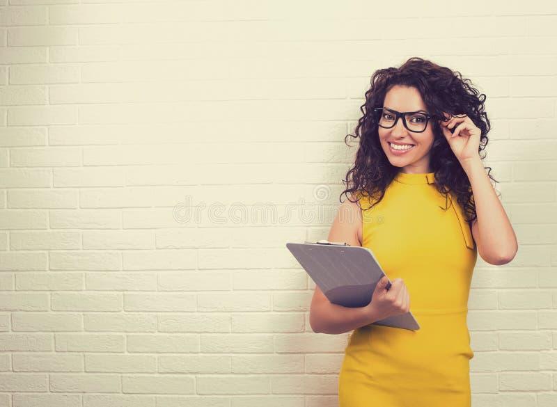 Glimlachende jonge bedrijfsvrouw op witte bakstenen muurachtergrond royalty-vrije stock afbeelding