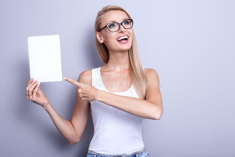 Glimlachende jonge blondevrouw met lege kaart stock afbeelding