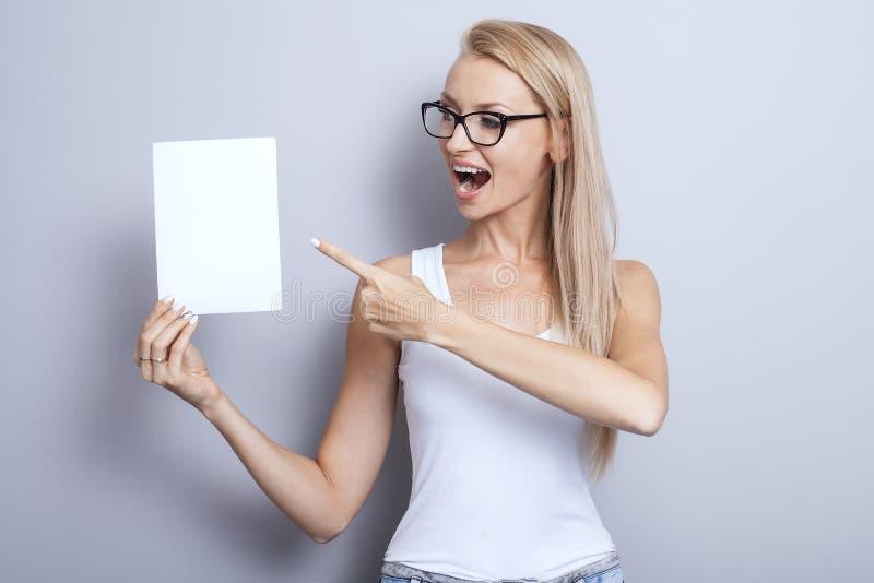 Glimlachende jonge blondevrouw met lege kaart stock fotografie
