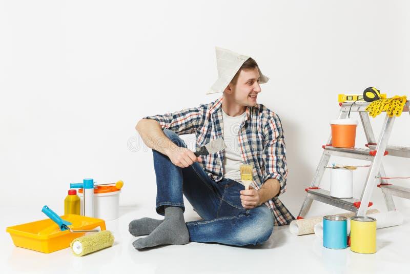 Glimlachende jonge die mens in krantenhoed met borstel, de instrumenten van het stopverfmes voor de ruimte van de vernieuwingsfla royalty-vrije stock foto