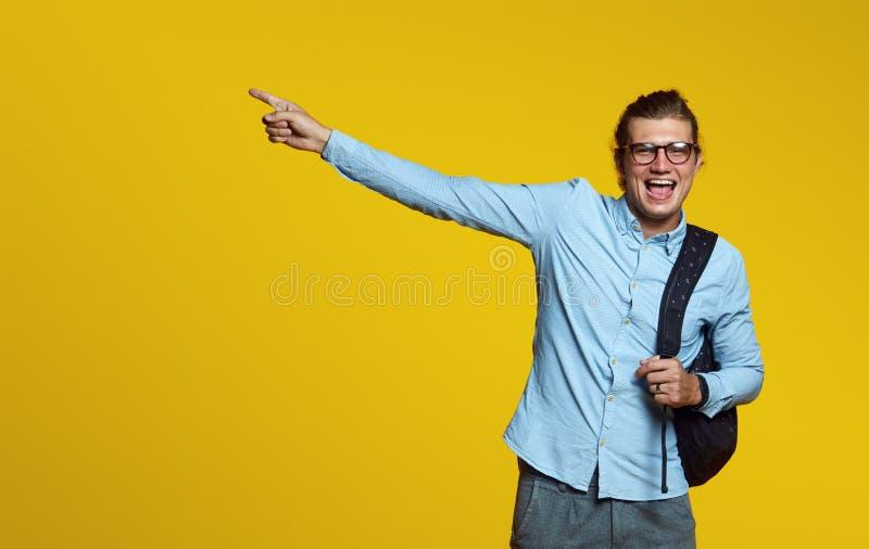 Glimlachende jonge die mens met oogglazen, houdend rugzak en richtend vinger weg op een gele achtergrond wordt geïsoleerd stock afbeelding