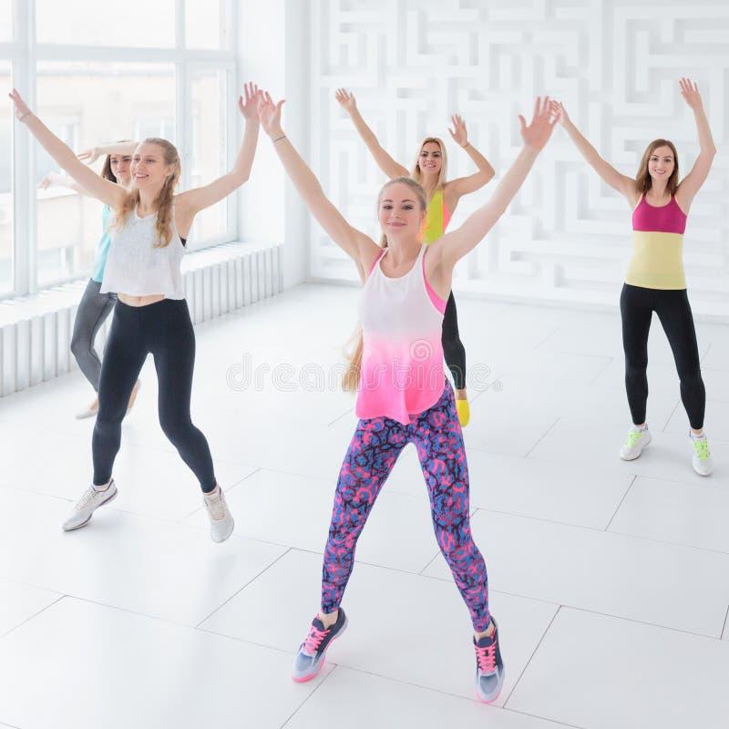 Glimlachende jonge die vrouwen met handen omhoog bij de klasse van de geschiktheidsdans in witte geschiktheidsstudio worden opgeh stock foto's