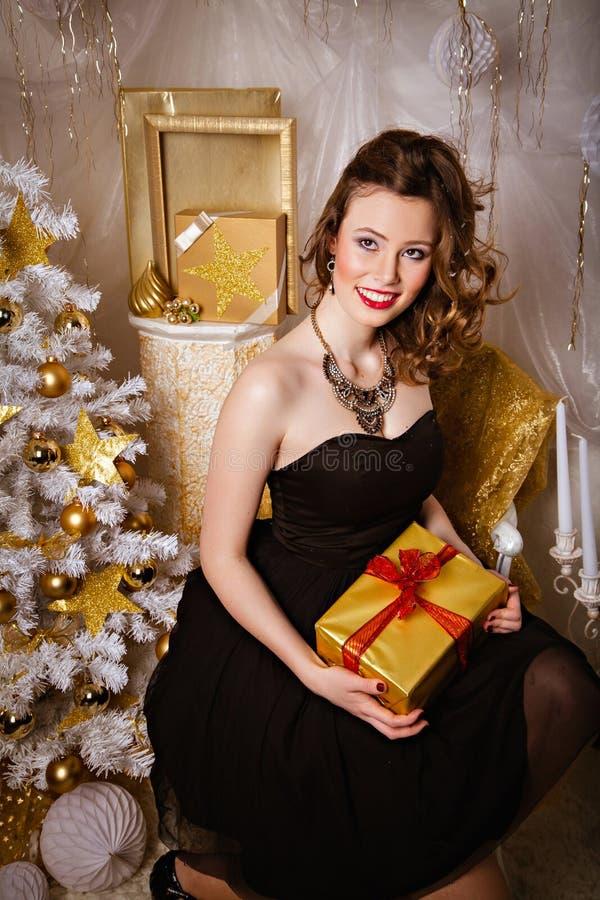 Glimlachende jonge donkerbruine vrouw dichtbij Kerstboom stock afbeeldingen