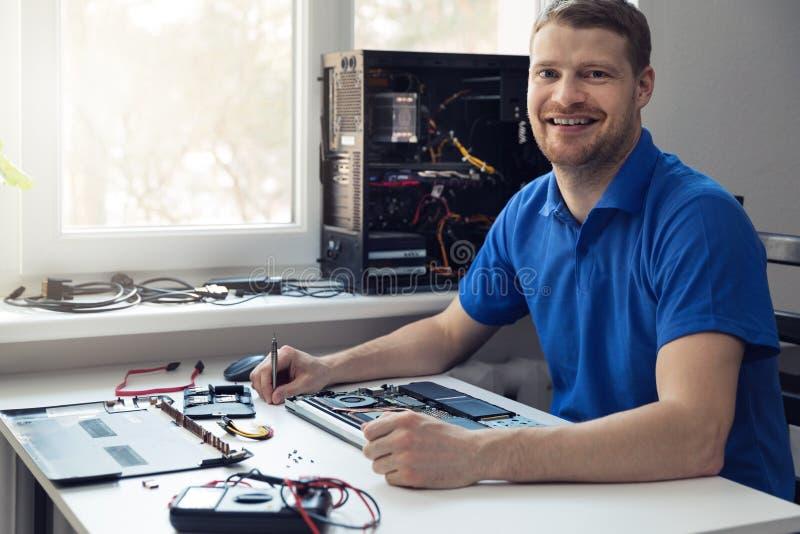 Glimlachende jonge elektronikatechnicus op het werk stock foto's