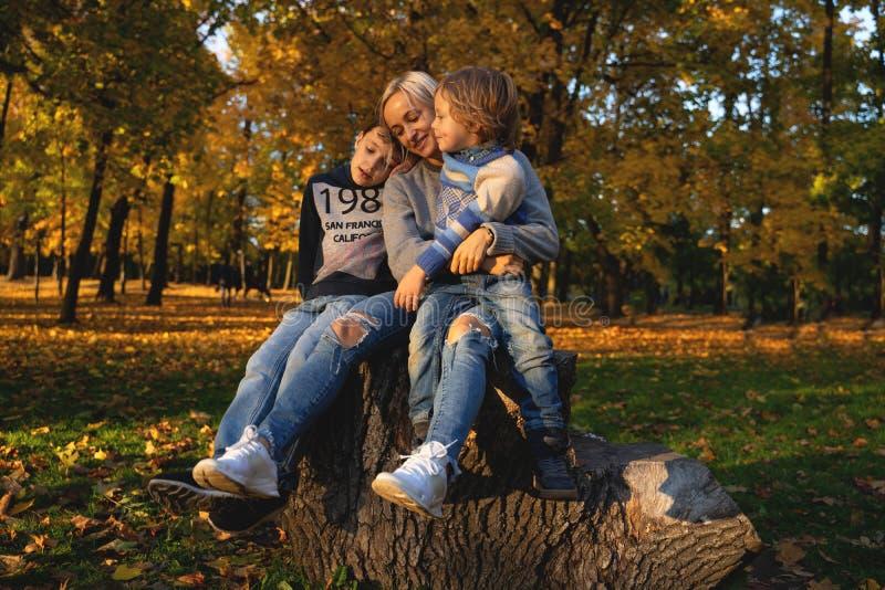 Glimlachende jonge familie in bladeren op een de herfstdag royalty-vrije stock afbeeldingen