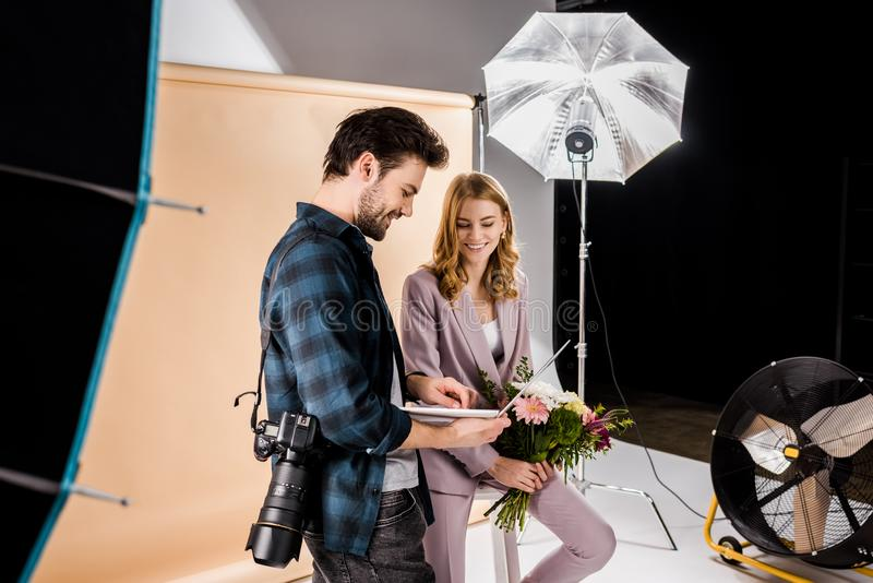 glimlachende jonge fotograaf die laptop tonen aan mooi vrouwelijk model royalty-vrije stock afbeelding
