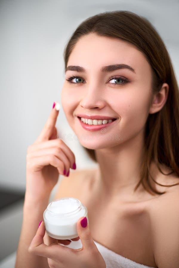 Glimlachende jonge gemengde rasvrouw die gezichtsroom op haar perfecte huid toepassen Model die met onberispelijke huid witte kru stock afbeelding