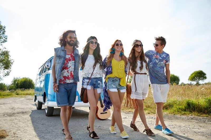 Glimlachende jonge hippievrienden over minivan auto stock afbeelding