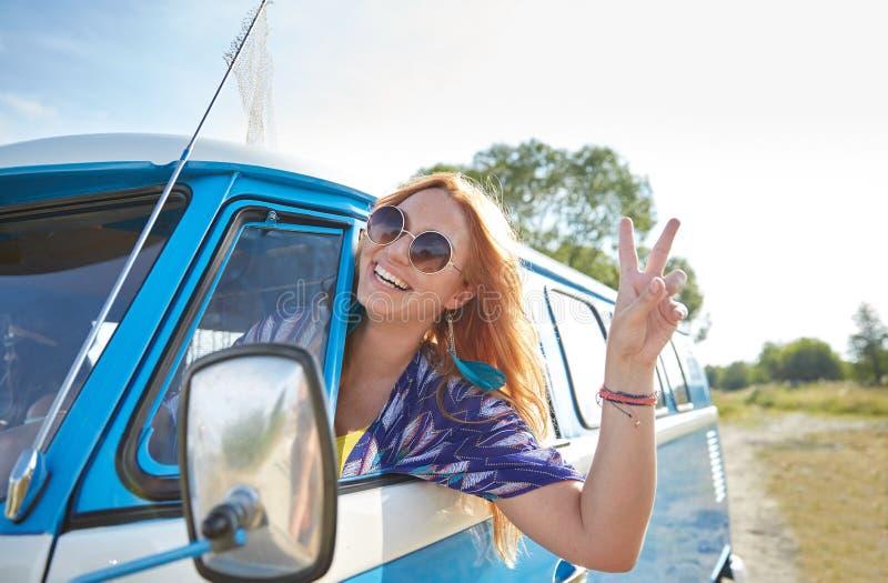 Glimlachende jonge hippievrouw die minivan auto drijven royalty-vrije stock afbeeldingen