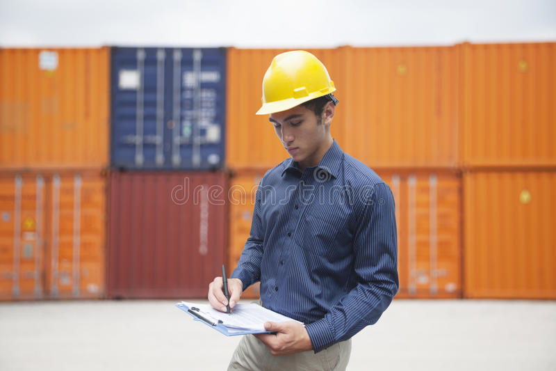 Glimlachende jonge ingenieur in beschermende het werkslijtage in een verschepende werf die lading onderzoeken en op klembord schri stock fotografie