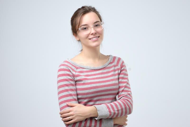 Glimlachende jonge Kaukasische vrouw met haar gevouwen wapens royalty-vrije stock foto's