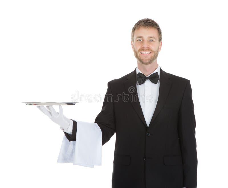 Glimlachende jonge kelner die leeg dienend dienblad houden royalty-vrije stock afbeeldingen