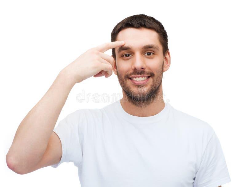 Glimlachende jonge knappe mens die aan voorhoofd richten stock afbeeldingen