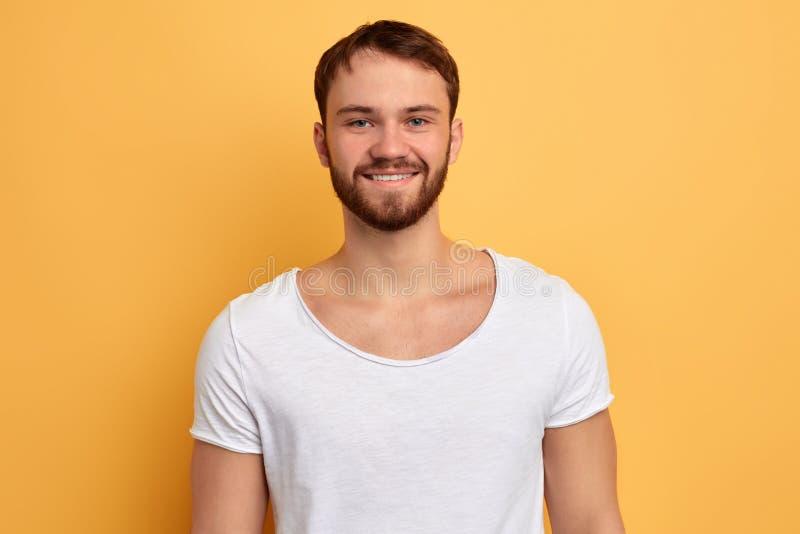 Glimlachende jonge knappe knappe mens in witte t-shirt stock afbeelding
