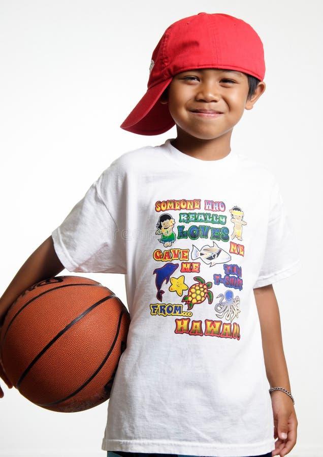 Glimlachende jonge knul die zijn basketbal houdt royalty-vrije stock afbeeldingen