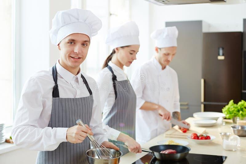 Glimlachende jonge kok in schort en hoed stock fotografie