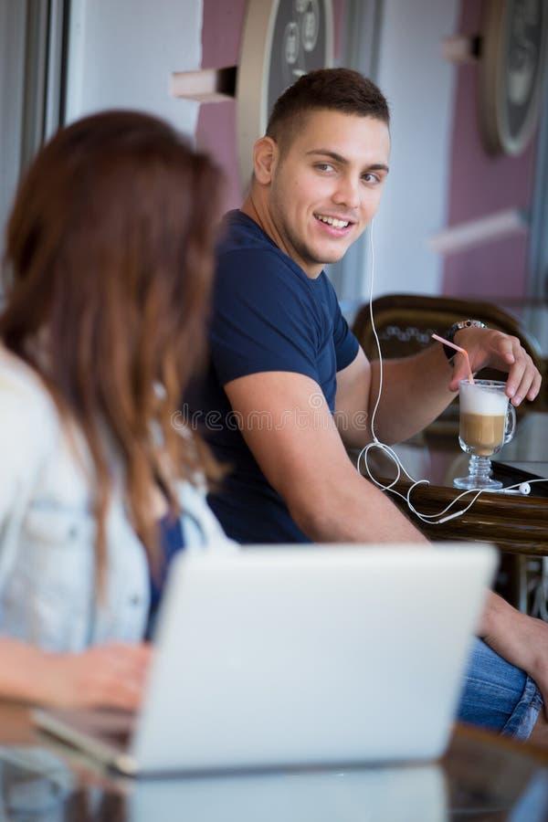 Glimlachende jonge man en vrouw in een koffie royalty-vrije stock afbeelding