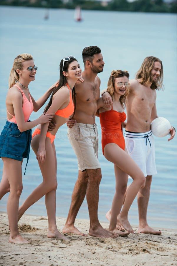 glimlachende jonge mannelijke en vrouwelijke vrienden die samen lopen royalty-vrije stock afbeelding