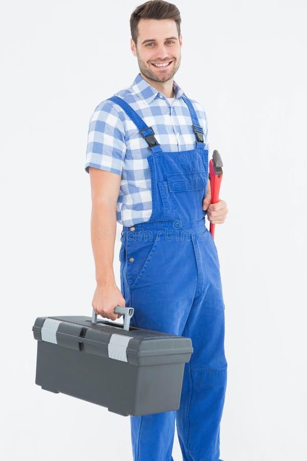 Glimlachende jonge mannelijke hersteller dragende toolbox stock foto's