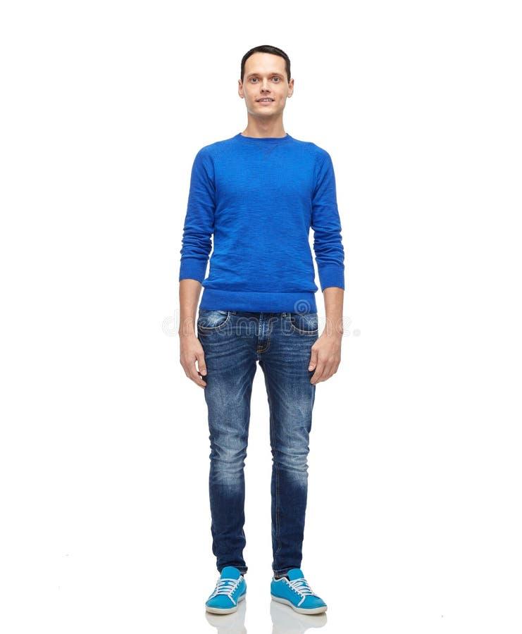 Glimlachende jonge mens in blauwe trui en jeans royalty-vrije stock fotografie
