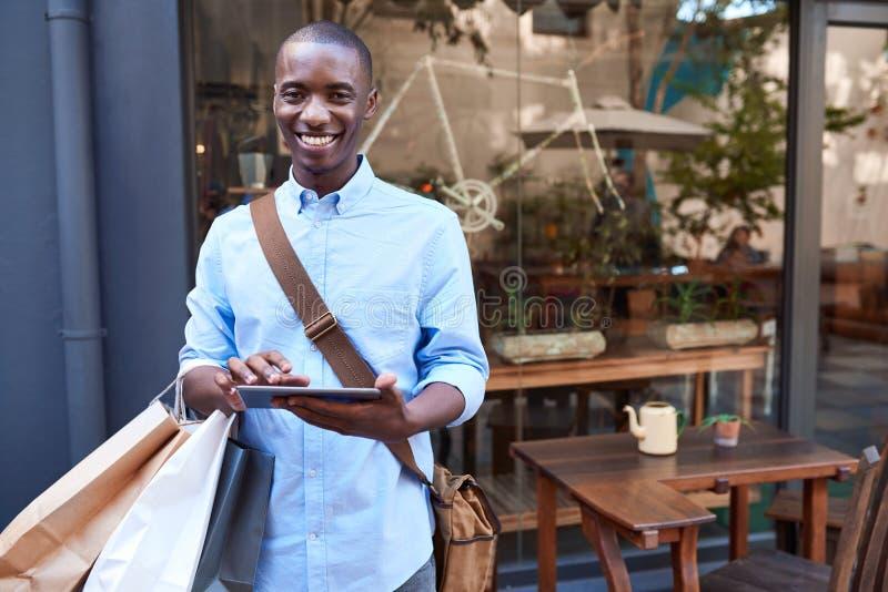 Glimlachende jonge mens die een digitale tablet gebruiken terwijl uit het winkelen royalty-vrije stock afbeelding