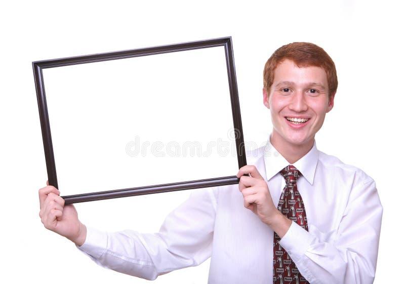 glimlachende jonge mens die een kader houden stock afbeelding