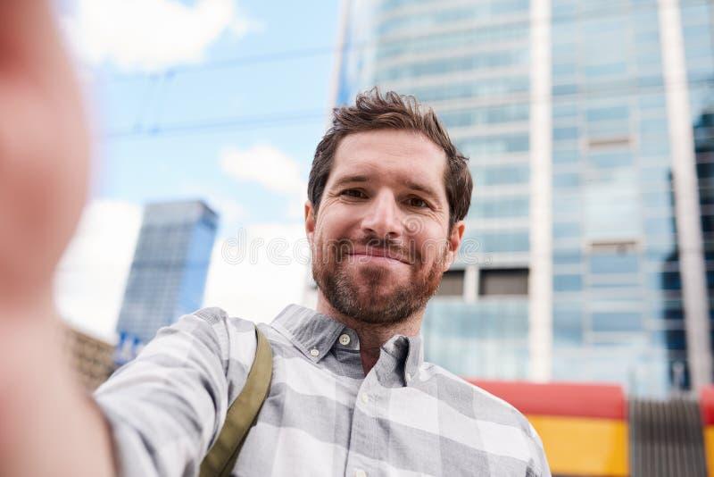 Glimlachende jonge mens die een selfie in de stad nemen stock fotografie