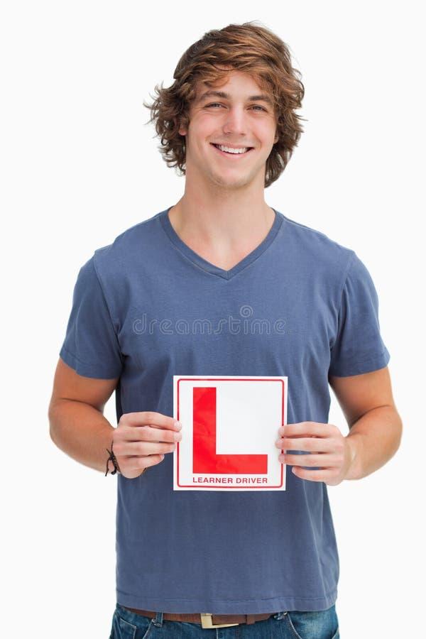 Glimlachende jonge mens die een teken van de leerlingsbestuurder houden stock afbeeldingen