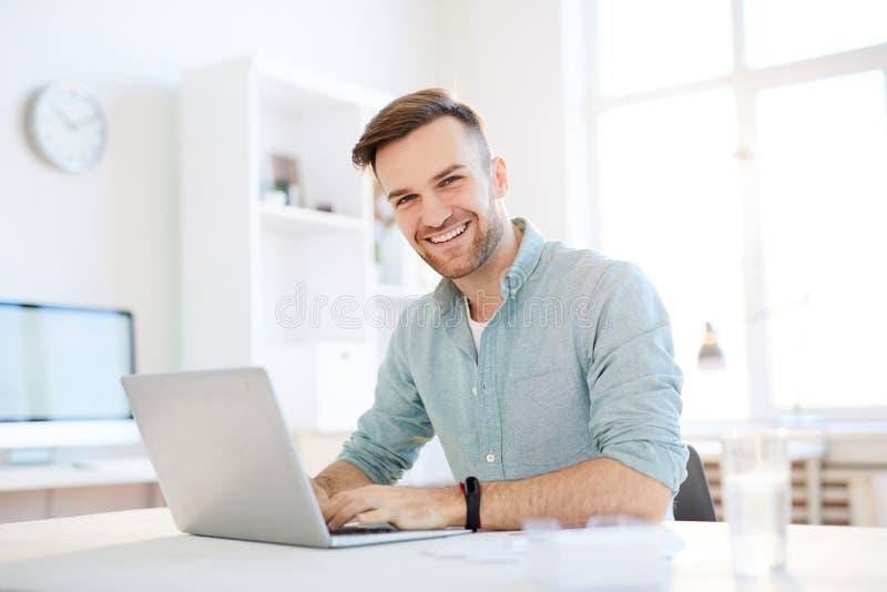 Glimlachende jonge mens die laptop met behulp van stock foto
