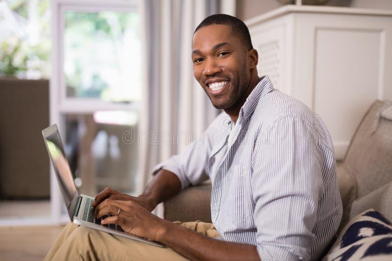 Glimlachende jonge mens die laptop thuis met behulp van stock afbeelding