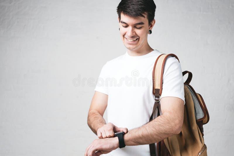 Glimlachende jonge mens die lege witte t-shirt, rugzak dragen en smartwatch stock foto's