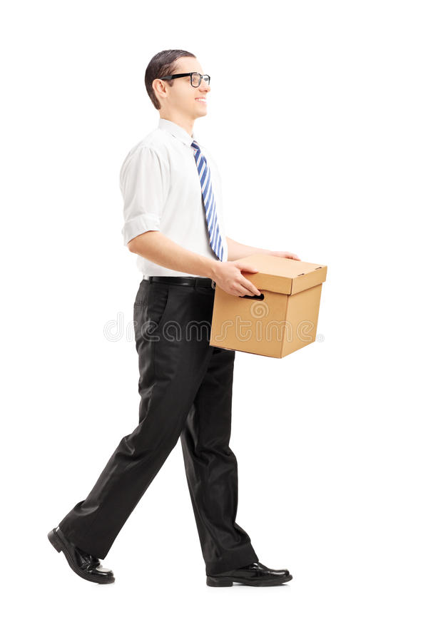 Glimlachende jonge mens die met een document vakje in zijn handen lopen stock foto's
