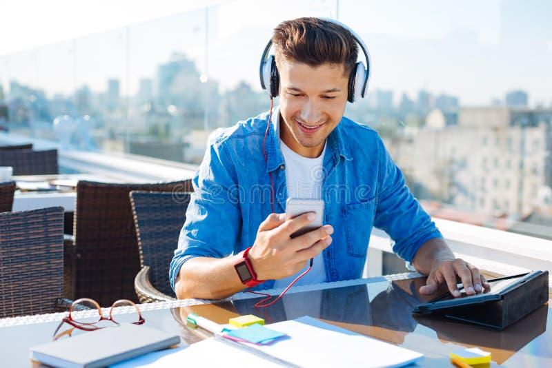 Glimlachende jonge mens die met hoofdtelefoon muziek kiezen om te luisteren royalty-vrije stock fotografie