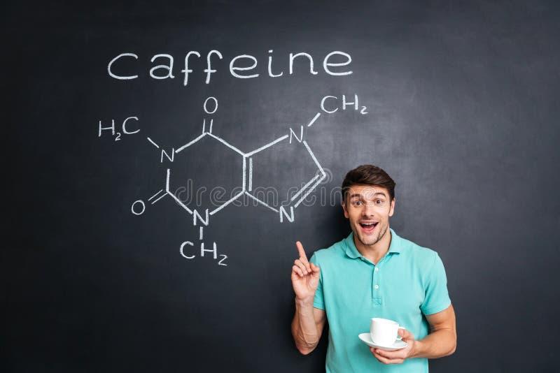 Glimlachende jonge mens die op de getrokken chemische structuur van de cafeïnemolecule richten stock fotografie