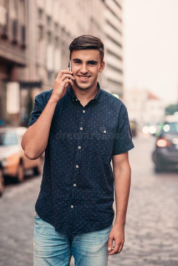 Glimlachende jonge mens die op een cellphone in de stad spreken royalty-vrije stock fotografie