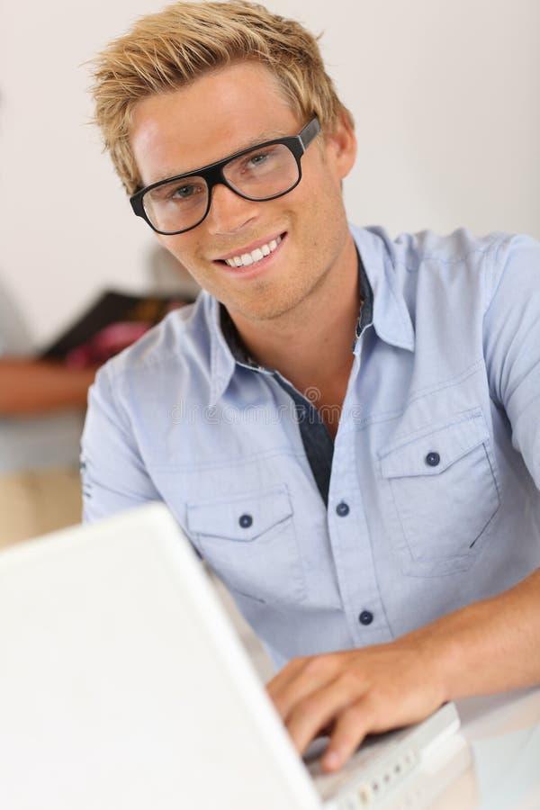 Glimlachende jonge mens die op kantoor werken stock afbeelding