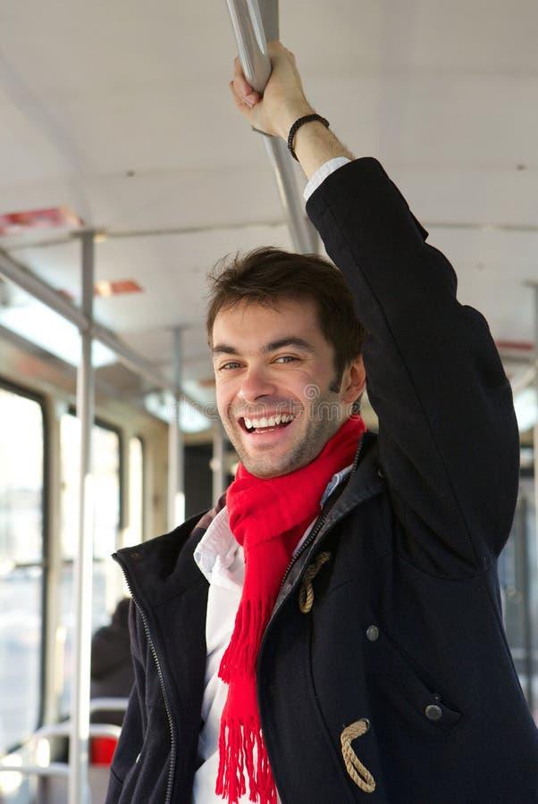 Glimlachende jonge mens die openbaar vervoer nemen stock foto's